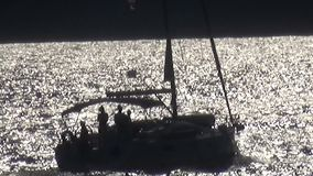 Yacht Traveling on the Gold Sea Surface. A yacht is traveling on the gold sea surface. Zoom out stock video footage