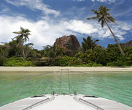 Yacht and tropical beach of paradise island. The luxury yacht arrived to the tropical island. Paradise beach is in-front and surrounded by palm-trees , rocks Royalty Free Stock Photo