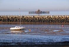 Yacht und aufgegebener Pier bei Ebbe Stockfotos