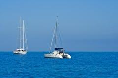 Yacht und Katamaran auf blauem Meer Lizenzfreie Stockfotos