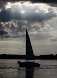Yacht under the celestial rays. Hand reaching for a ray of light on the sky royalty free stock images