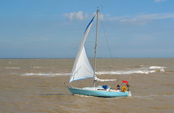 Yacht under sail at the estuary of the river Deben at Felixstowe Ferry. Felixstowe, Suffolk, England - August 07, 2016: Yacht under sail at the estuary of the Royalty Free Stock Image