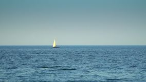 The yacht is under sail floats in the sea. Against the background of the blue sky stock video footage