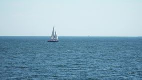 The yacht is under sail floats in the sea. On the horizon are seen cargo ships stock footage
