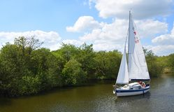 Yacht under sail navigating the river Bure near Horning, the Norfolk Broads. HORNING, NORFOLK, ENGLAND - MAY 10, 2018: Yacht under sail navigating the river royalty free stock photos