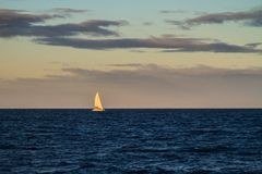 Yacht under Sails at Dusk Royalty Free Stock Images