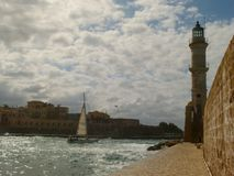 The yacht under the snow-white sail goes to the exit from the harbor of Chania at the lighthouse stock photos