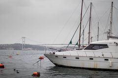 Yacht waiting moored at the port and the bridge in the background. royalty free stock image
