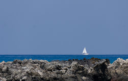 Yacht with white sail goes by rocks of Kaunaoa Beach Royalty Free Stock Photo
