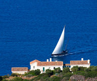 Yacht with white sail swim to the shore of Crete. Stock Photo