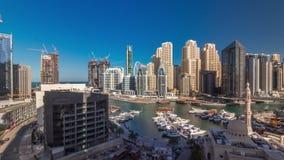 Yachten in Dubai Marina, flankiert von der Al Rahim Moschee und Wohntürmen und Wolkenkratzer aus der Luft Zeitplanung stock footage