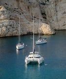 Yachten in einer Bucht unter Felsen Stockbilder