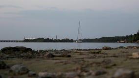 Yachten fortskrider floden på bakgrunden av fördämningen arkivfilmer