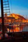 Yachten gegen Schloss in der Nacht Alicante Stockfotografie