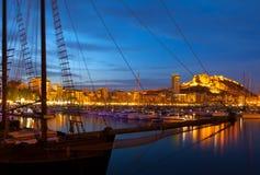 Yachten gegen Schloss in der Nacht Alicante Stockbilder