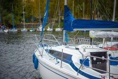 Yachten mit gefalteten Segeln auf dem Ufer nahe dem Pier Lizenzfreies Stockfoto