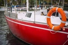 Yachten mit gefalteten Segeln auf dem Ufer nahe dem Pier Lizenzfreies Stockbild