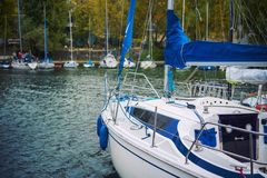 Yachten mit gefalteten Segeln auf dem Ufer nahe dem Pier Stockfotos