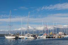 Yachten nahe dem Pier auf dem Hintergrund von Bergen Stockfotos