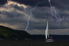 Yachten på havet, kommer närmare en åskväder med regn och blixt på bakgrund royaltyfri fotografi