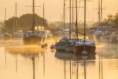 Yachter som förtöjas på soluppgång på den dimmiga floden Arkivfoton