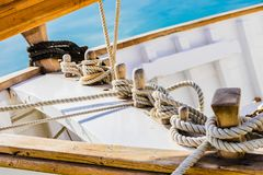 Classical wooden sailing boat deck with tied nautical ropes on wood cleats. Yachting background of old sailboat, detail closeup of wooden cleats with tied stock photography