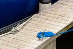 Yachting, blue rope and mooring bollard. On bridge in port of sailing Stock Photography