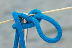 Yachting, blue rope on sailboat, details of yacht, sea background. Yachting, blue coiled rope on sailboat, details and part of yacht on sea background Stock Image