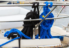 Yachting, coiled rope on deck of sailboat, details of yacht. Yachting, coiled black and blue rope on deck of sailboat, details and part of yacht Royalty Free Stock Images