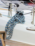 Yachting, coiled rope on sailboat, details of yacht. Yachting, coiled rope and bollard on sailboat, details and part of yacht Royalty Free Stock Photo