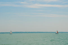 Yachting competition on Lake Balaton, Hungary. Two sailing boats on foreground under beautiful blue sky with clouds. Two sailing boats on foreground under Stock Photo