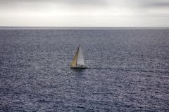 Small single-masted sailing yacht on background of weak waves. Yachting in Northern seas. Small single-masted sailing yacht on background of weak waves. Even Royalty Free Stock Images