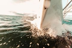 Yachting on sail boat bow stern shot splashing water royalty free stock images