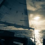 Yachting on sail boat during sunny dark weather stock photo