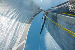 Yachting, sailing, competition, cruise, regatta, freedom, adventure concept. Close up of yacht mast and silver sail with yellow sl Stock Photos