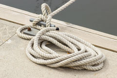 Yachting, white rope and mooring bollard. Yachting, rope and mooring bollard on bridge in port of sailing Stock Images