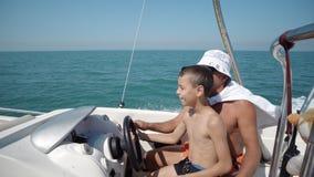 Yachtkapitänhand auf Yachtlenkrad Lokaler Mann, der einem kleinen Jungen beibringt, wie man ein Yachtboot auf parasail Adrenaline Stockfotografie