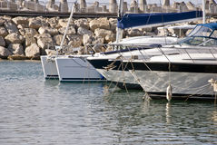 Yachts. Beautiful   white and black yachts moored to wharf at the harbor Royalty Free Stock Images