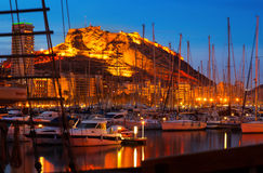 Yachts against Castle in night. Alicante Stock Photos
