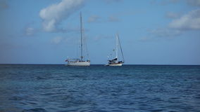Yachts at anchor in the tropics. Two sailboats with sails furled at admiralty bay, bequia stock footage