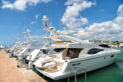 Yachts in bay with cloudy sky. Luxury yachts docked in the port in bay at sunny day with clouds on blue sky in La Romana, Dominican Republic Stock Photography