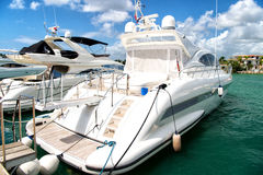 Yachts in bay with cloudy sky. White luxury yachts docked in the port in bay at sunny day with clouds on blue sky in La Romana, Dominican Republic Royalty Free Stock Photo