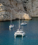 Yachts in a bay among rocks. Yachts in a bay on a roadstead among rocks Stock Images