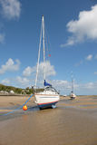 Yachts, beach mooring. A channel at low tide on a beach with moored yachts with a blue cloudy sky in the distance Royalty Free Stock Photo