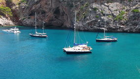 Yachts in beautiful bay with crystal clear water, Sa Calobra, Mallorca, Spain stock video footage