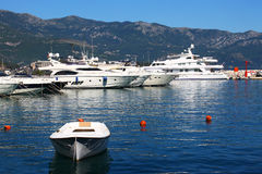 Yachts and boat anchored in port near mountains. Here are many expensive yachts and one small boat anchored in a small port on a lake near a mountain area Royalty Free Stock Photography