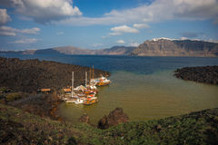 Yachts and boats in the bay at the volcanic island of Nea Kamen Stock Image