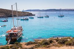 Blue lagoon comino. Yachts and boats bring tourists to the beautiful crystal clear azure turquoise blue waters of the Blue Lagoon on the small holiday island of Stock Images