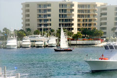 Yachts and boats in harbor. Scenic view of yachts and leisure boats in harbor with apartment or hotel buildings in background Royalty Free Stock Photos