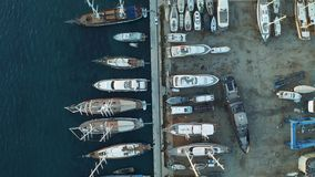 Yachts and boats moored at the dock shipyard. Aerial view from above. 4k stock video footage